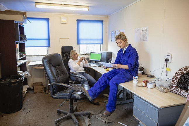 A side-view shot of two female farmers sitting in their office talking, they are discussing a to do list over a cup of tea.